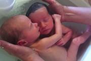 Νεογέννητα δίδυμα απολαμβάνουν το μπάνιο τους αγκαλιασμένα