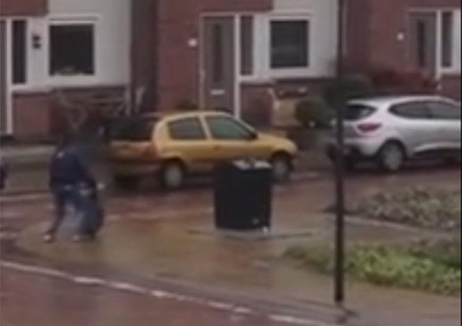 Άνδρας προσπαθεί απεγνωσμένα να πετάξει τα σκουπίδια του σε παγωμένο πεζοδρόμιο