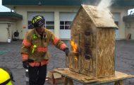 Πυροσβέστης δείχνει τα βασικά της φωτιάς χρησιμοποιώντας ένα κουκλόσπιτο